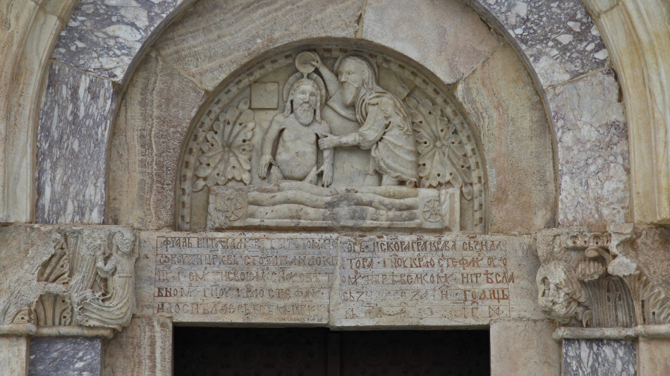 tympanum of John the Baptist baptizing Christ Jesus and lintel thanking Catholic Franciscan monk and architect Fra Vita